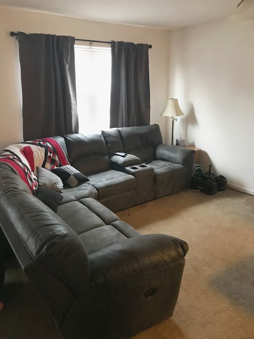 Living space includes section couch that has a recliner on both ends.
