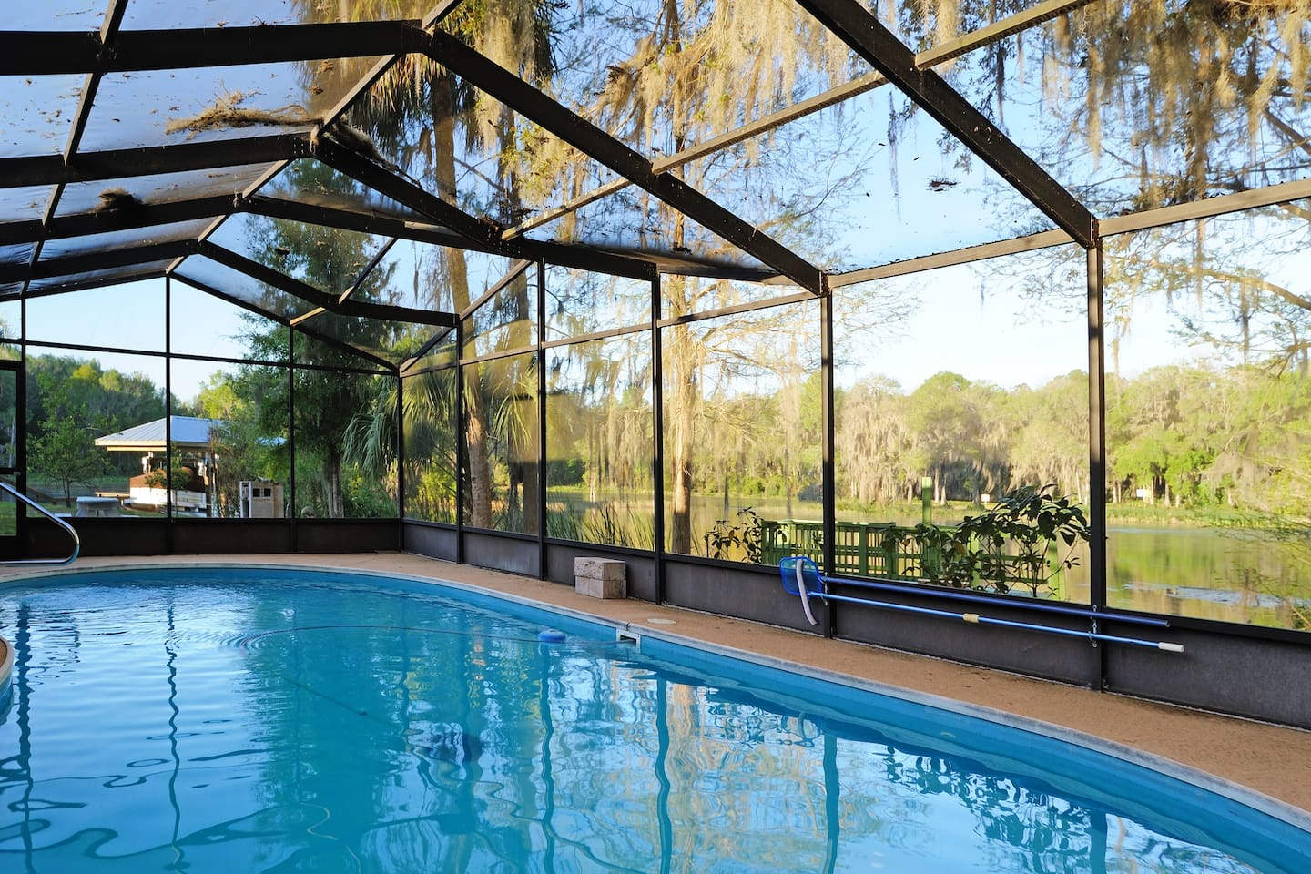 view of our enclosed pool,  just steps from the Rainbow river! Kayaks are waiting!