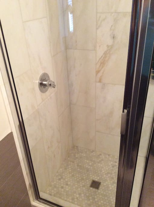 Marble tiled shower in private bath.