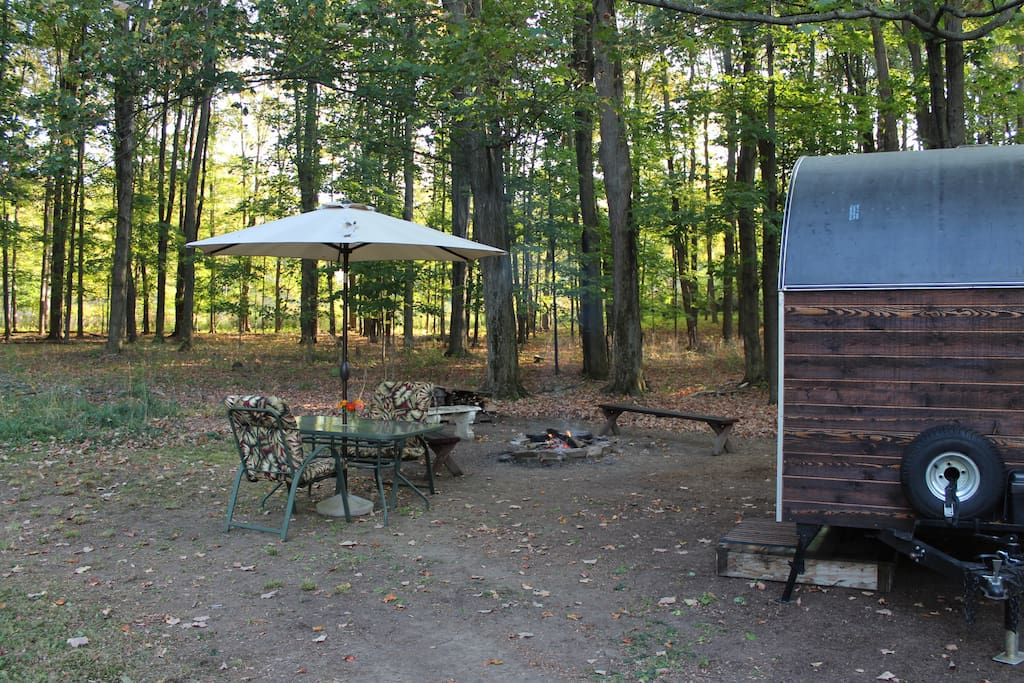 Accommodations complete with glass table, comfy chairs, umbrella, campfire, and firewood