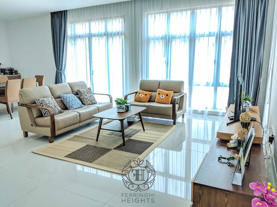 """Ground floor: Large living room with elegant sofa, coffee table, 40"""" LED TV and ceiling mounted air-conditioner"""