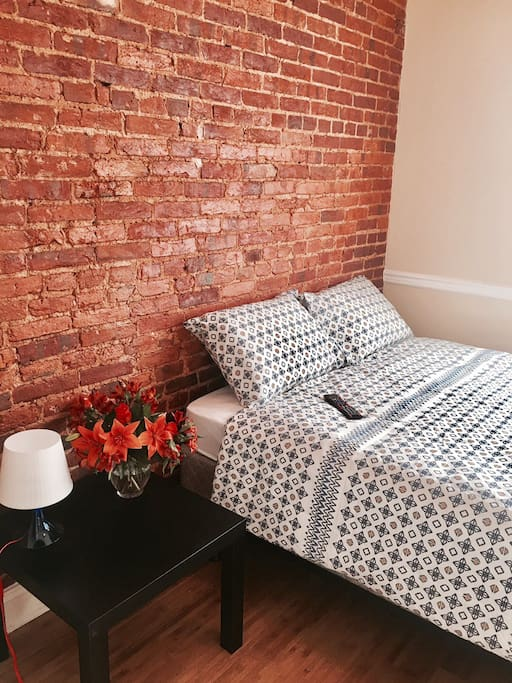 Queen bed with exposed brick