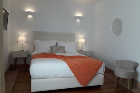 Quarto de casal com ambiente minimalista, em tons de laranja.