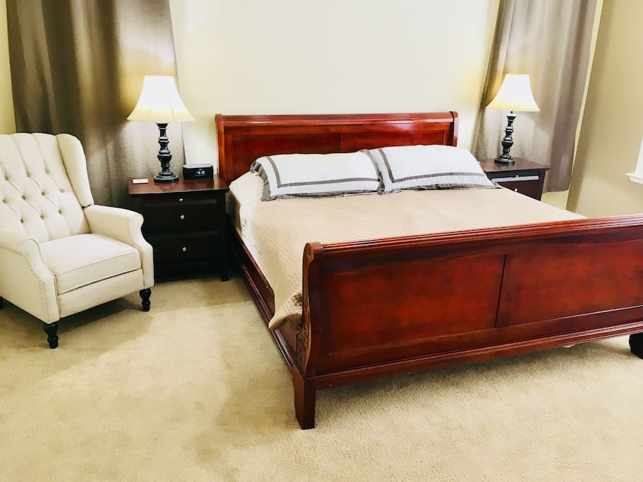 Large master bedroom with king size bed and accent chair