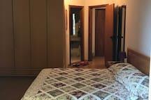 Cama de casal, em quarto espaçoso com ar condicionado e sacada.