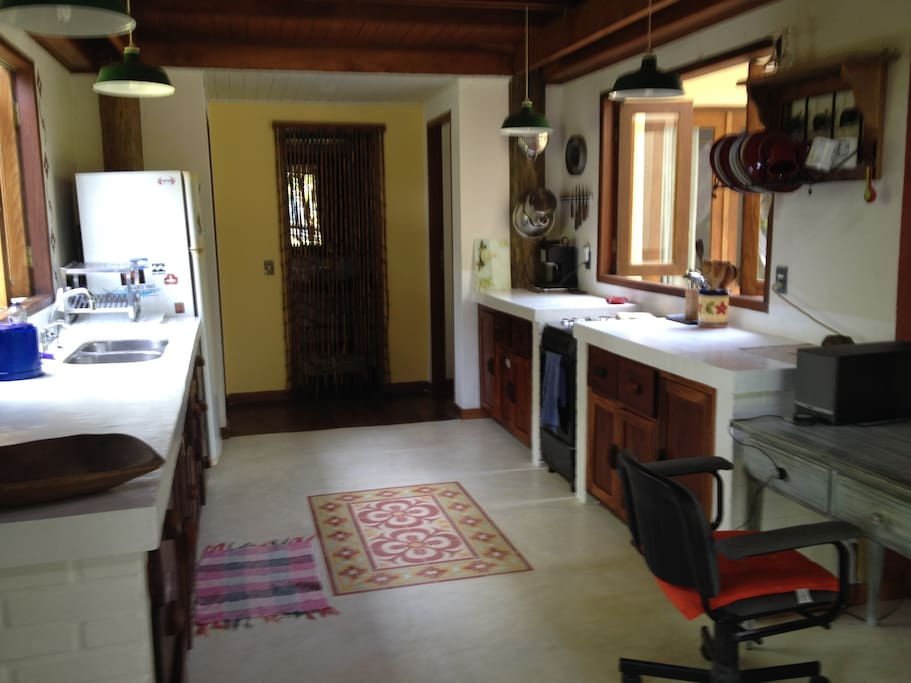 Large kitchen with burned cement counter tops, lots of storage and desk