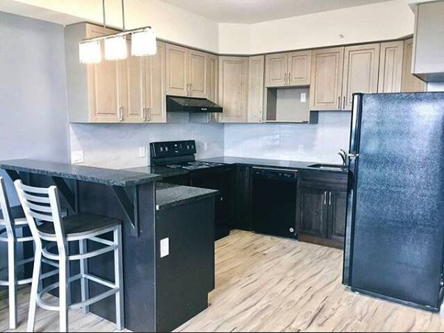 Beautiful open concept kitchen  fully equipped with a dishwasher, bar stools, fridge, microwave, oven and more!