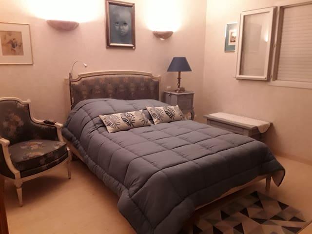 Chambre bleue chez hôtes accueillants.