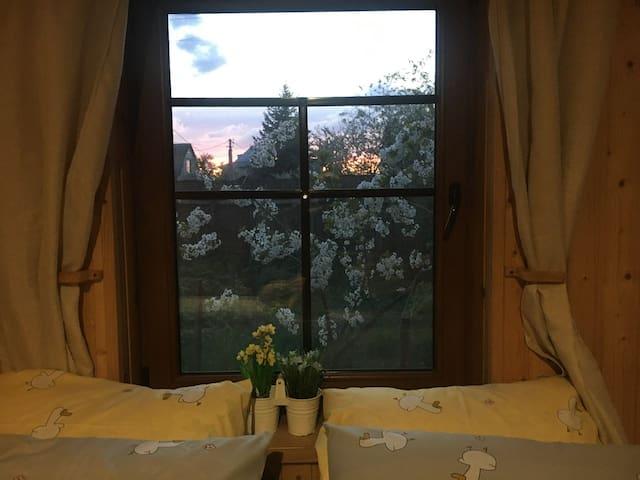 Окно над двухспальной кроватью  в большой комнате.