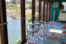 This is the best private dining seat in town! A table for two overlooking the harbor with hand-painted stools.