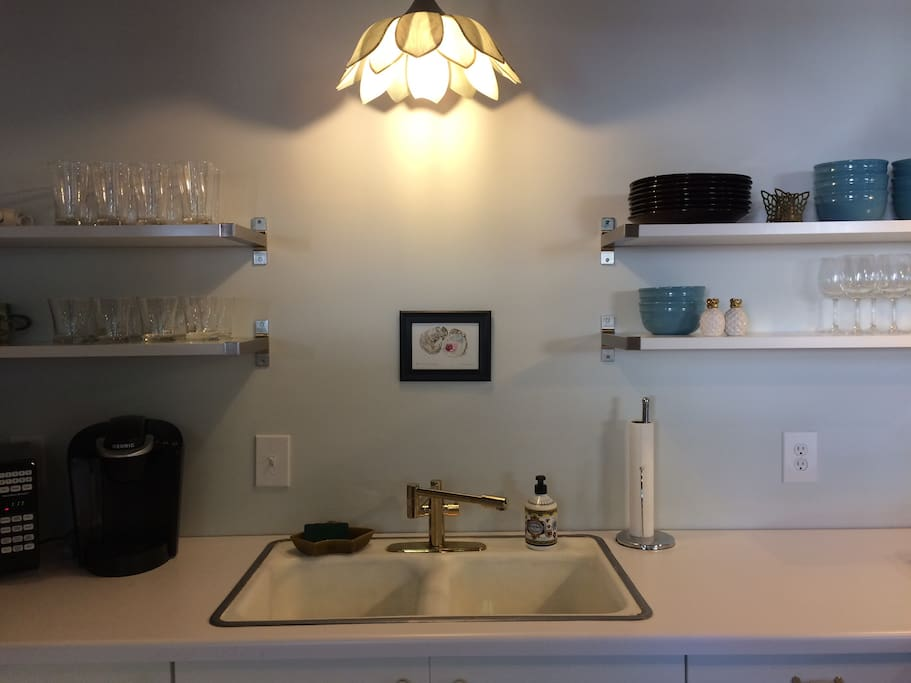 Open shelving, original porcelain sink and an antique magnolia light fixture in kitchen.