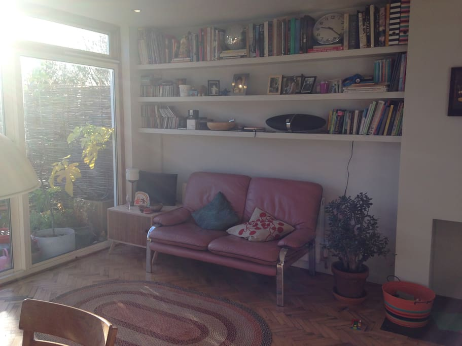 Pink sofa in the kitchen and lots o books.