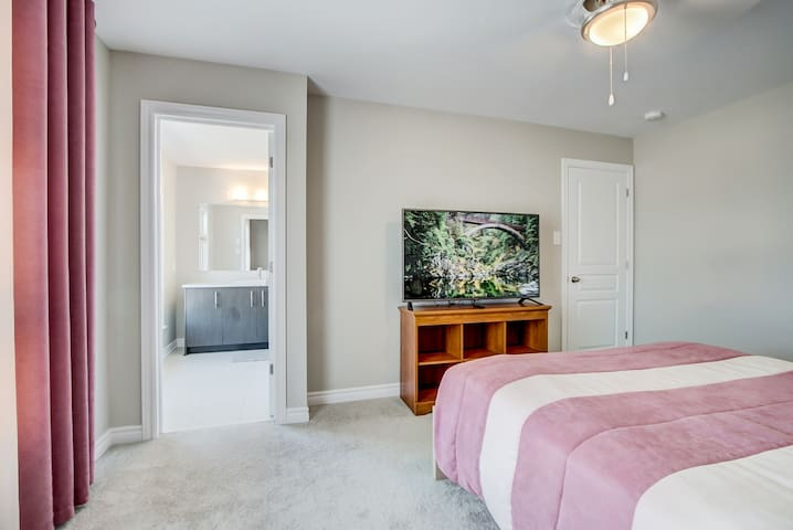 Deluxe Bedroom with private bathroom, TV and storage. Queen size bed.