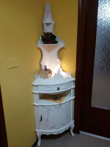 l ingresso è arredato con questo mobiletto particolare bianco, e una panca tutta imbottita di pelle bianca