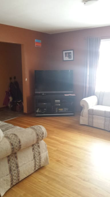 """living room with couch and love seat, plus 50"""" tv, playstation and cable"""