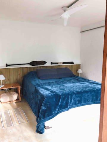 Segunda suíte andar inferior: cama de casal, cortinas blackout, ventilador de teto e chuveiro elétrico.