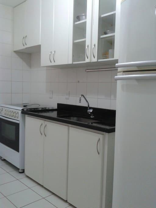 Cozinha com utensilios de cozinha, microondas geladeira duplex ,