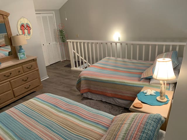 Cozy upstairs loft features 2 full beds, flat screen tv, and a full bath.