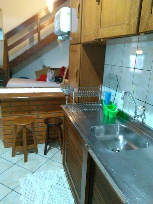 Cozinha com fogão, geladeira, microondas e máquina de lavar.
