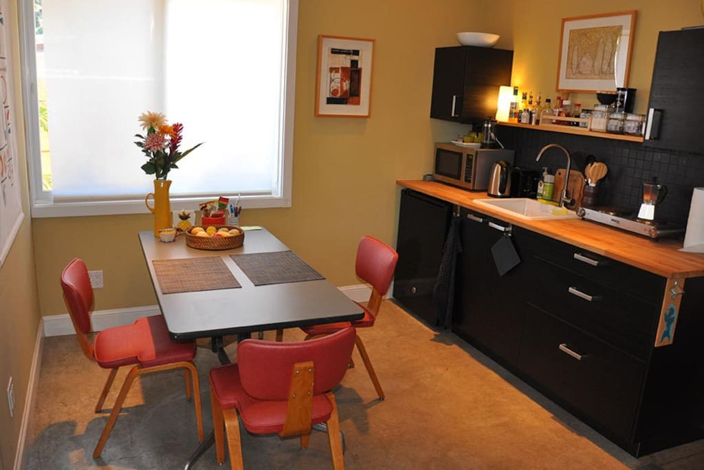 Cozy kitchen and dining. Simple galley-style kitchen with stove top, microwave, electric kettle and small under-counter refrigerator. Stocked with basics - tea, coffee, milk, breakfast needs, herbs + spices, olive oil, etc.