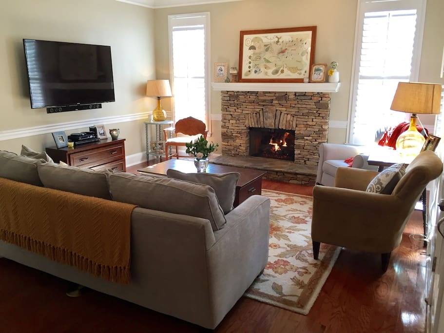 Living Room with gas fireplace, 60 inch screen TV, cable with DVR, DVD Player, and Bluetooth sound system with surround sound speakers for playing music