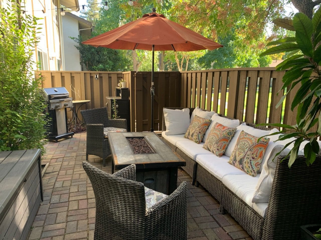 Back patio with fire pit and bbq grill in background.