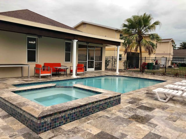 Heated salt water pool with a spa , sitting aria ,lounge chairs and dining table