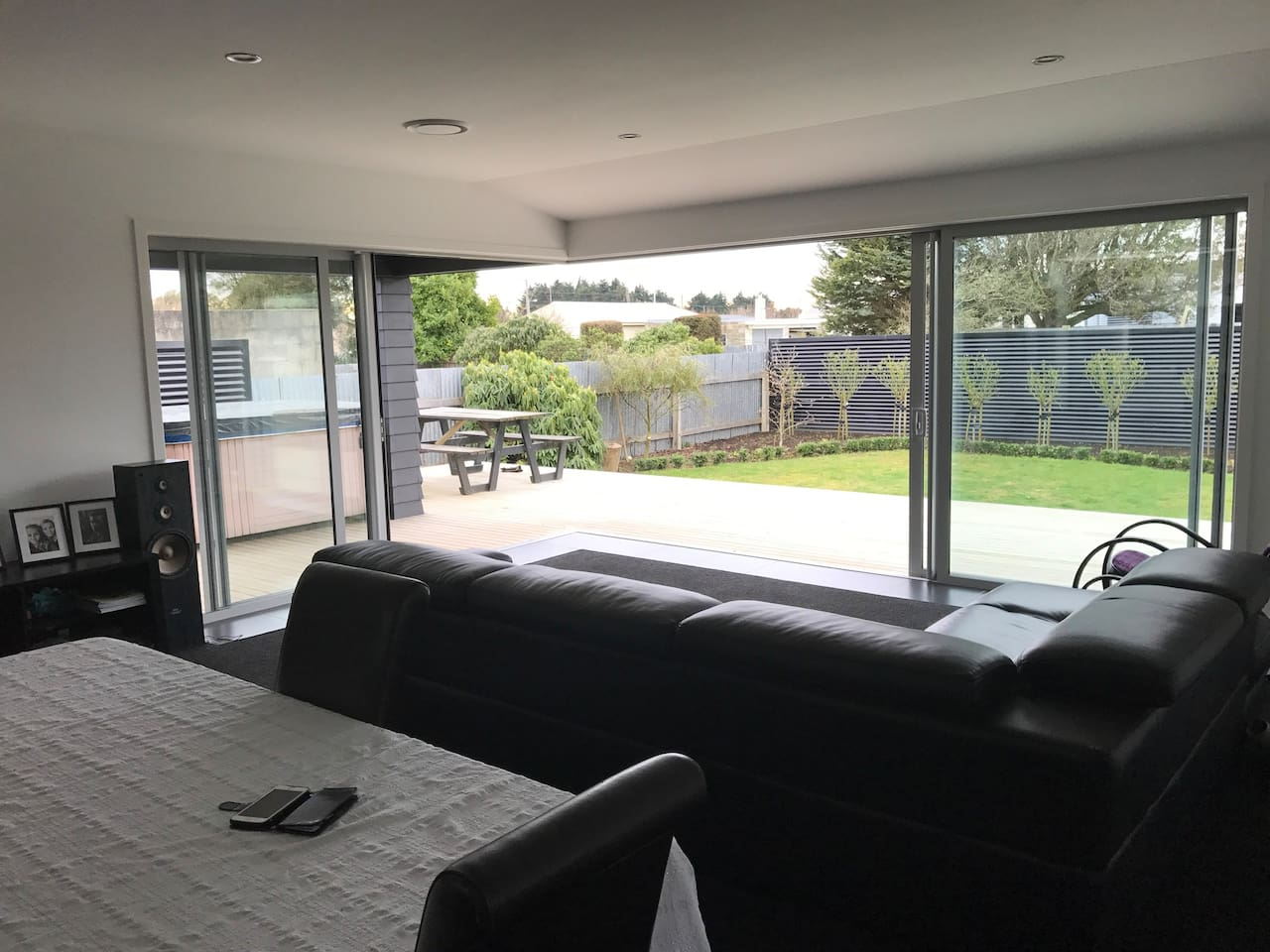 Living room with corner euro sliders opening onto large deck with spa pool. Perfect for summer nights.