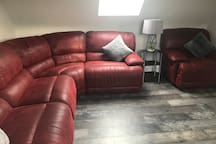 Bright Spacious modern living room area. Corner sofa with recliners.