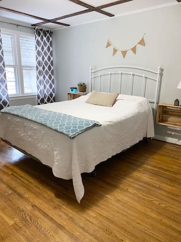 The main bedroom boasts a comfy queen-sized bed and a large, walk-in closet complete with shelving and hangers for convenience.   Baby playpen is also kept in closet and can be pulled out when needed.