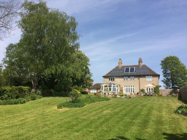 View of the back of the house from halfway down the long south facing garden. All the main rooms face the garden and have far-reaching views. The house sits high up on a very quiet lane 5 minutes walk from the town centre.