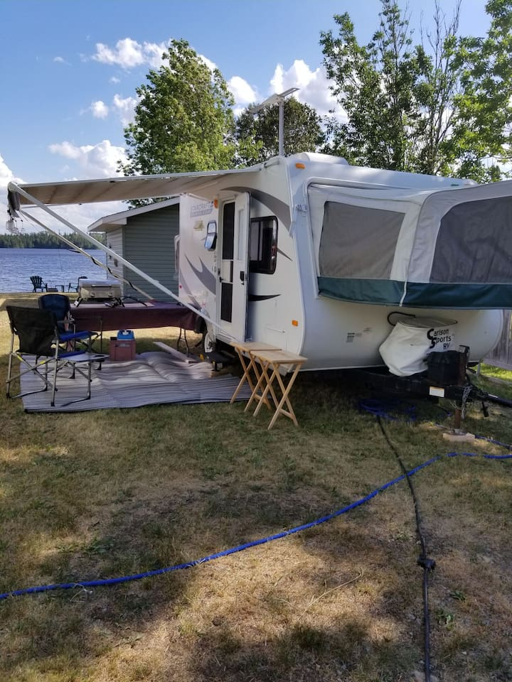 17.5 hybrid camper fully equipped and all set up on Kenogami lake (outskirts if Kirkland lake).  Enjoy the Lakeview and Lake access. There is an extra spot on the dock to tie a boat. There's a 14-foot aluminum boat and a 9.9 motor that can be rented