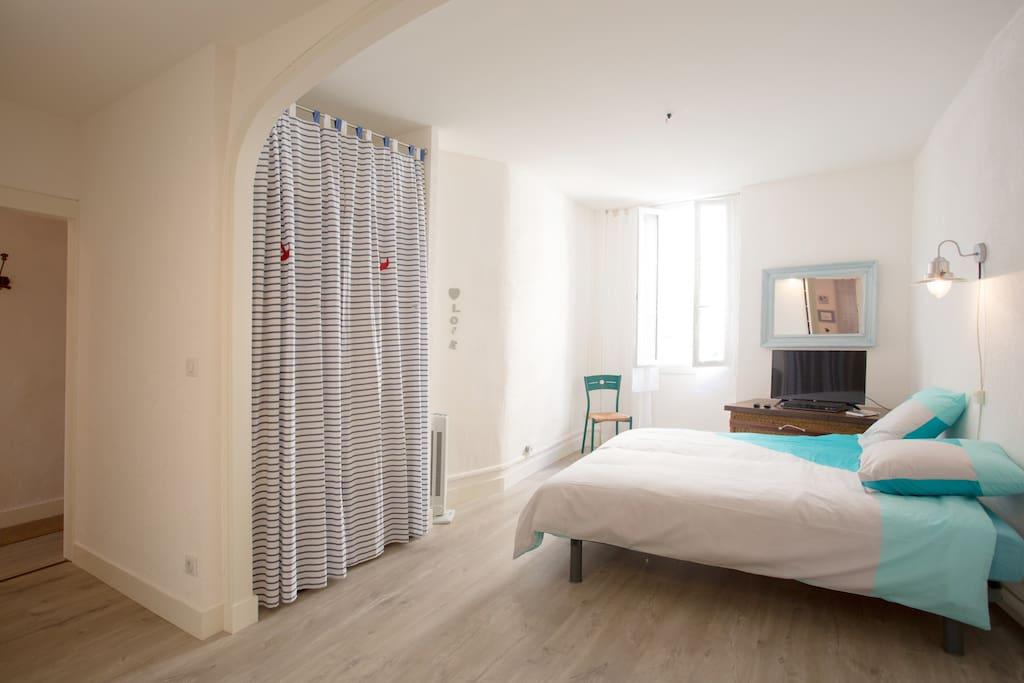 La chambre avec lit double et plusieurs rangements.