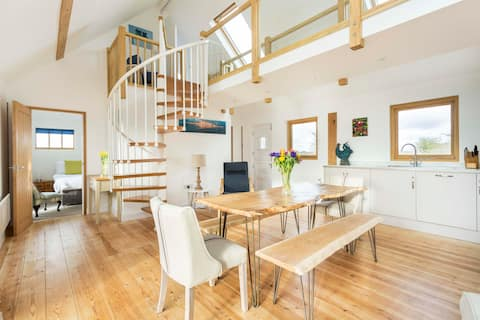 Light and airy living room and kitchen with spiral staircase leading to the walkway between the twin bedded room and sitting room.