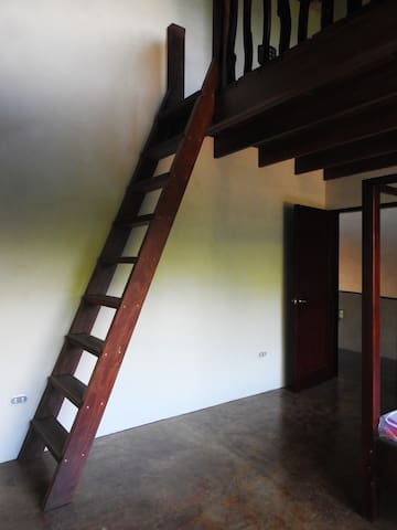 Access to the loft where a queen size bed awaits.