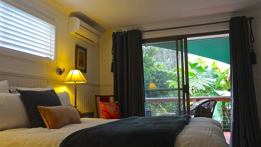 Bedroom looks over a tropical garden and over a lovey sunny deck perfect for breakfast or enjoying a drink