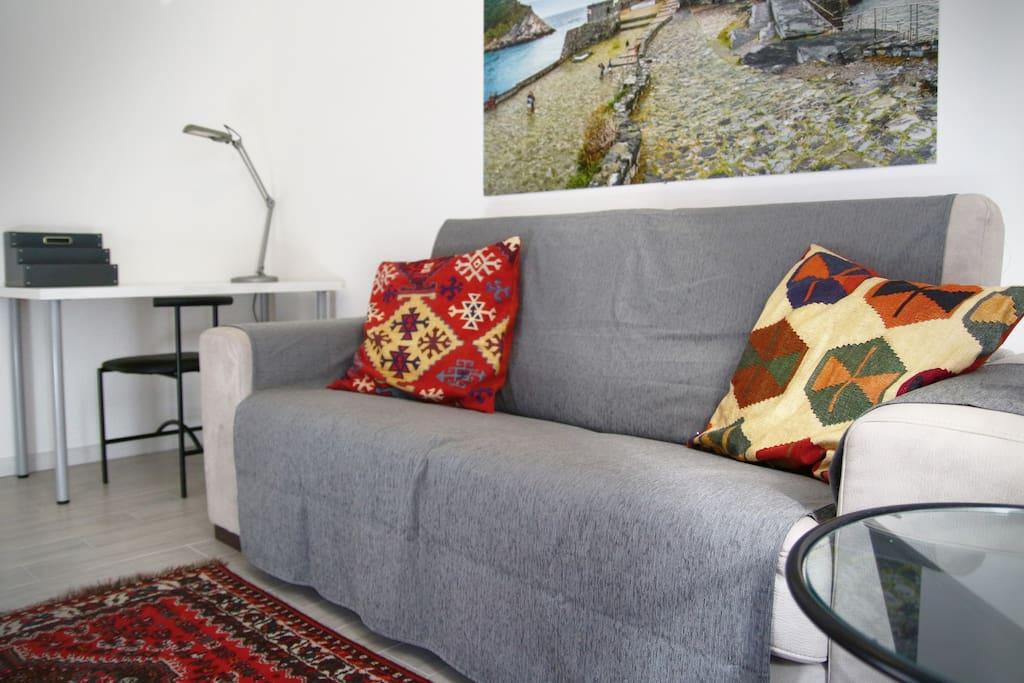 Salotto con divano letto e scrivania