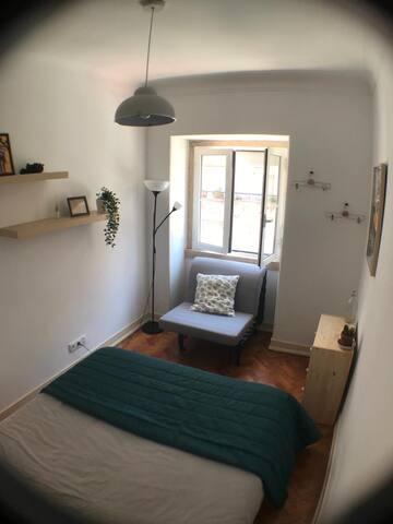 Quarto equipado com cama queen size, sofá e comoda e cabide para roupas