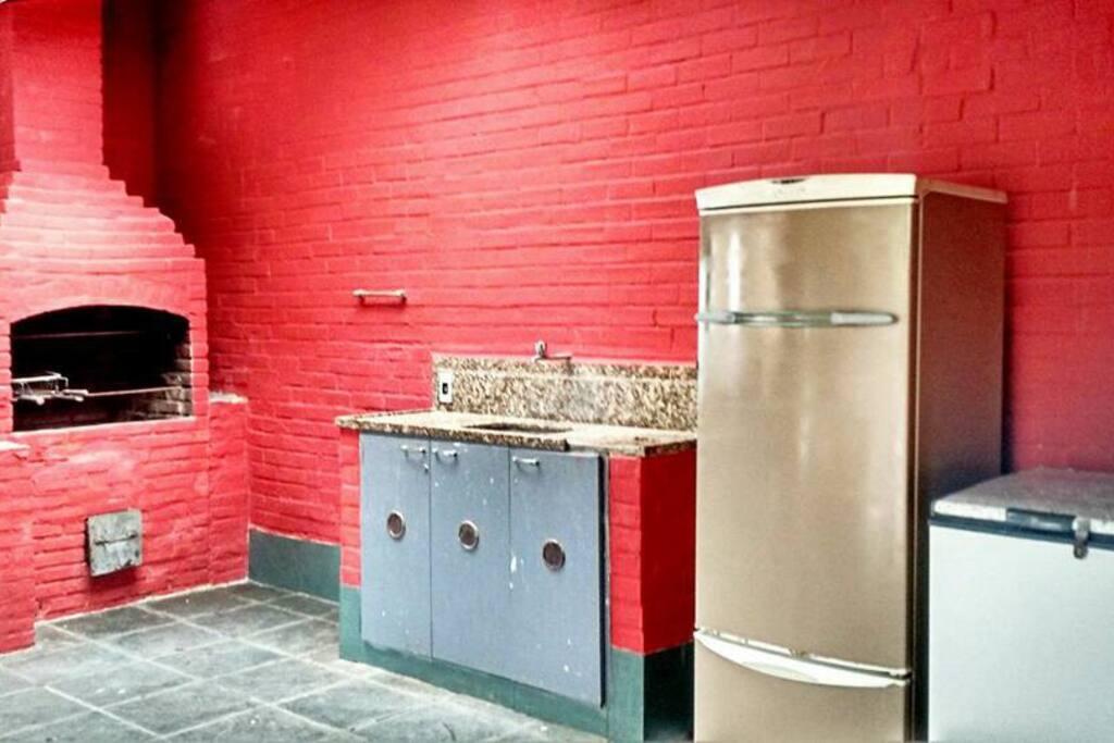 Espaço com churrasqueira com bancada e 3 geladeiras disponíveis.