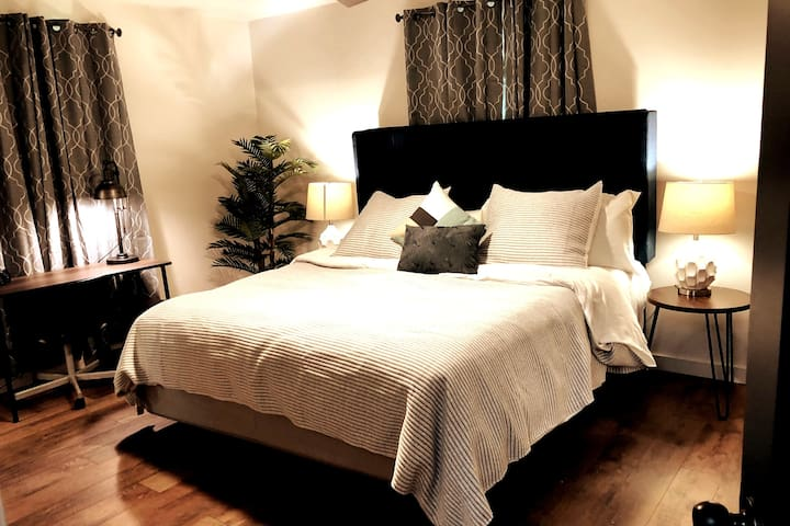 Master bedroom with King Sleep Number bed. Feel free to change the setting while you are here to the most comfortable way for you to sleep. Each side has its own setting. My sleep number setting is 45.  This room also has a small desk on the left.