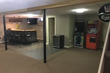Basement with wet bar, shuffle board and arcade games.