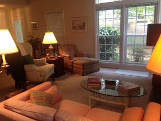 Lots of natural night in comfortable living room with love seat, 2 upholstered chairs and large HD TV.