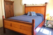 Separate bed room has a  queen size bed, extra pillows and blankets, bed stands, dressers, a closet with hangers, an iron, ironing board, a vacuum and an air conditioner in the summer.