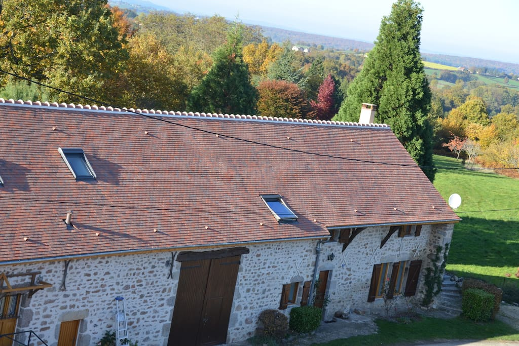 Vue aérienne de la maison entourée de verdure, prés, forêts, chemins de randonnée.