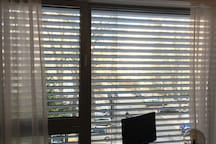 The  bedroom window is wall-to-wall and floor-to-ceiling with electric exterior blinds and inerior privacy curtains. Desk with screen keyboard, mouse and laptop connection