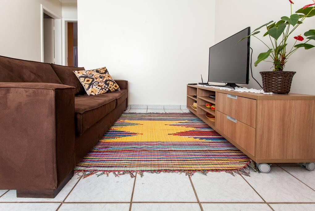 Vista da sala de estar, na entrada do apartamento. No detalhe, TV a cabo LED Smart sobre rack.