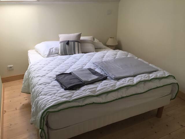 Chambre 1, lit 140 cm, linge fourni. Portant dans la chambre; penderie et commode sur palier face à la chambre. Store occultant.