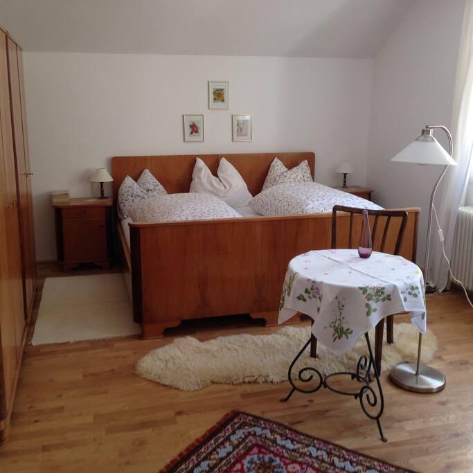 Geräumiges Zimmer mit Doppelbett, Lesegelegenheit und Klavier