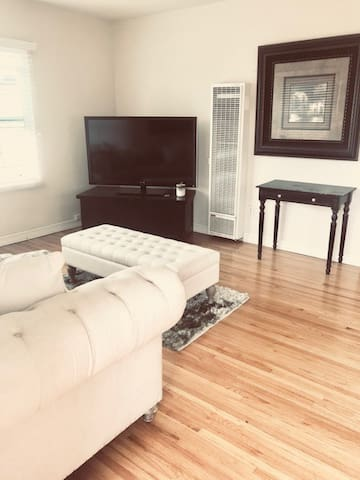 Living room view from front door. Lovely hardwood floors and flat screen TV with local channels