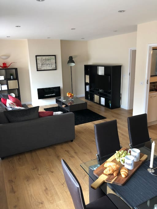 A very spacious living room which is full of modern and stylish furniture along with a designer dining room table and 6 chairs.
